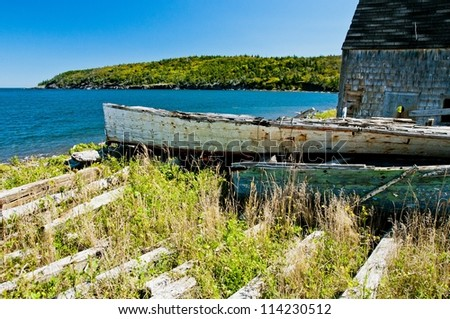 rural scene from cape breton island,small boat hauled up and seemingly rotting where it sits - stock photo