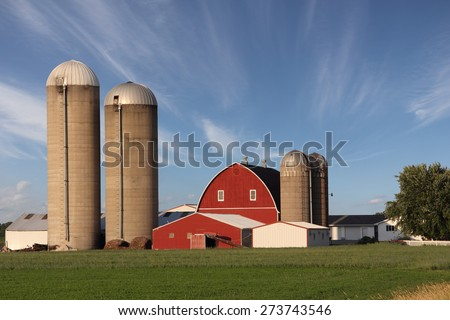 Rural scene showing a modern family farm with a bright red barn surrounded by silos.  Dramatic blue sky with wispy clouds.  The sky also provides text space if needed. - stock photo