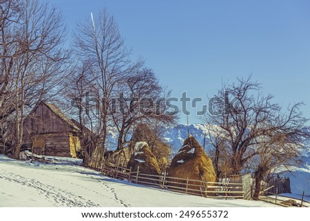 Rural scenery with ancient traditional Romanian farm on a winter sunny day in Magura village, Brasov county, Romania. - stock photo