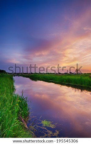 Rural summer sunset landscape with river and dramatic colorful sky