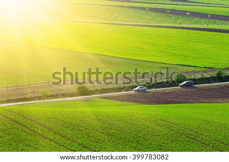 Rural sunny landscape with green wavy fields, road and cars, South Moravia, Czech Republic - stock photo