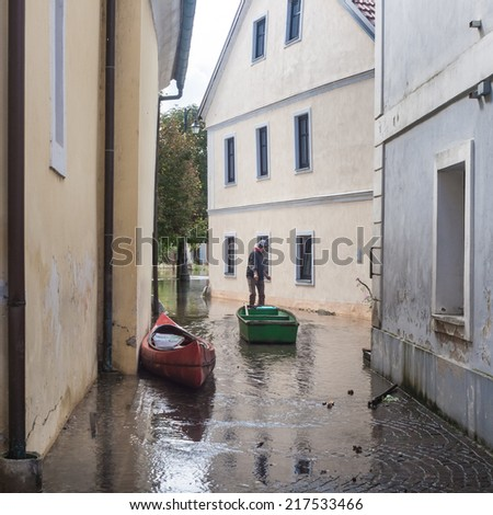 Rural village houses in floodwater. Road with the river overflown with the residents in their homes. Floods and flooding the streets. Natural disaster.   - stock photo