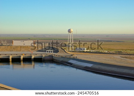 Rural water tower sits near an aqueduct.  - stock photo