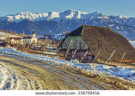 Rural winter scenery with old traditional wooden cottage and thawed snowy country road in Magura village, Romania. - stock photo