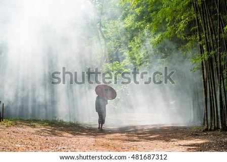 Rural woman walk with red umbrella