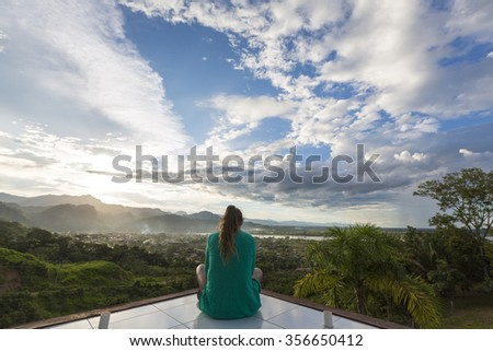 RURRENABAQUE, BOLIVIA, JANUARY 7: Woman sitting and meditating in front of an aerial panoramic view of Rurrenabaque, the gateway to the Bolivian Amazon rainforest. Bolivia 2015