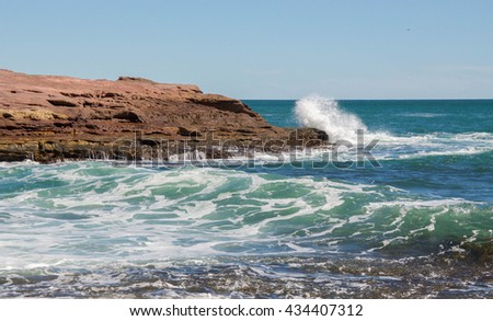 Rushing Indian Ocean waters on the Western Australia coastline with red sandstone under clear skies at Pot Alley beach in Kalbarri/Wave Spraying Sandstone/Pot Alley, Kalbarri, Western Australia - stock photo