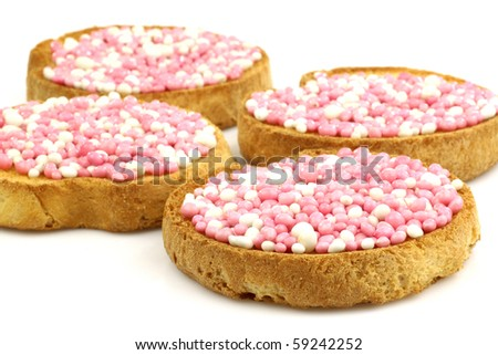 rusks with white and pink anise seed sprinkles served in Holland when a baby girl is born on a white background - stock photo