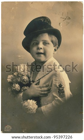 RUSSIA - CIRCA 1917: Retro postcard with weathered edges on white background printed in circa 1917, Russia. Vintage photograph depicts a young boy with a bouquet of flowers - stock photo