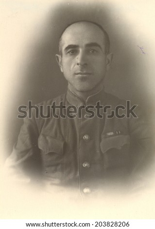 Russia, - CIRCA 1947s: An antique studio portrait of middle-aged man in a uniform with ribbons.