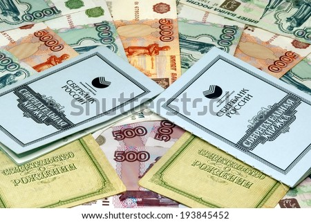 "RUSSIA - JANUARY 21, 2011: Russian money, savings book and birth certificates. In Russia pay for the birth of the second child money. The inscription in Russian ""Sberbank of Russia"", ""savings book"" - stock photo"