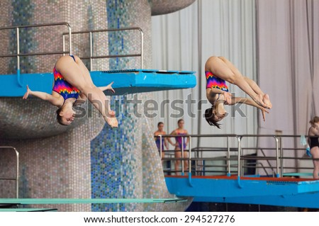 RUSSIA, MOSCOW - APRIL 29 2015: Athletes N. Aminieva and G. Sitnikova jump from diving-tower in Pool on Moscow city diving tournament in Moscow, Russia, 2015 - stock photo
