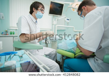 RUSSIA, MOSCOW - AUG 31, 2015: Dentist and his assistant preparing for oral examination of patient, young female patient sitting in chair in dental office of Center Endosurgery