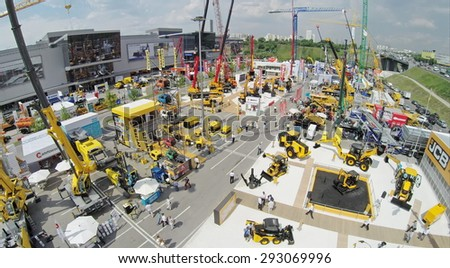 RUSSIA, MOSCOW - JUN 6, 2014:  People walk by International Specialized Exhibition of Construction Equipment and Technologies CET 2014 at Crocus Expo. Photo with noise from action camera - stock photo