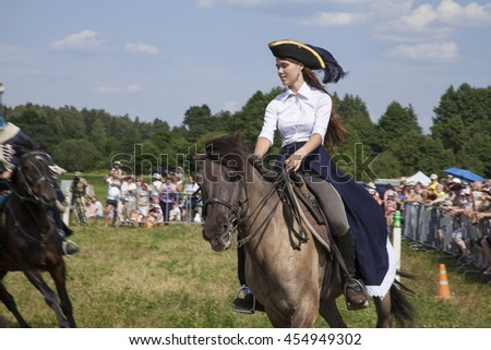 Russia, Moscow region, village Dushonovo-July 02, 2016: Young girl riding a horse in a hat with a feather and skirt the Amazon.