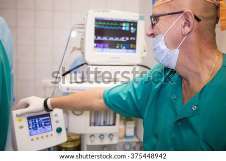 RUSSIA, MOSCOW - 01 SEP, 2015: Doctor in uniform is standing near heartbeat monitor at the center of endosurgery and lithotripsy.