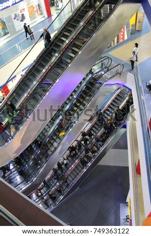 Russia, Murmansk - October 28, 2017, with people moving between the floors of the shopping center on the escalators