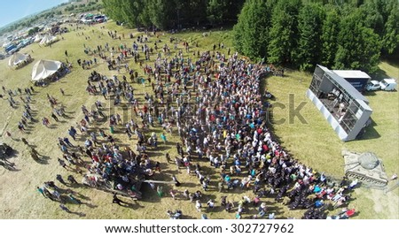 RUSSIA, NELIDOVO -?? JUL 12, 2014: Crowd of people listen concert during reconstruction Battlefield at Second World war. Aerial view. (Photo with noise from action camera) - stock photo