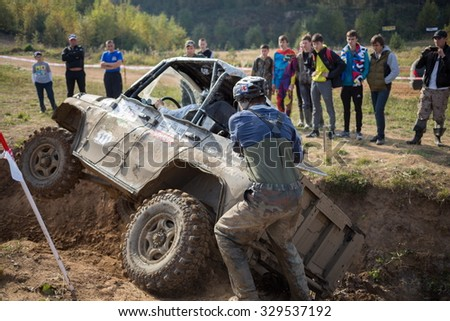 RUSSIA, PUSHKINO -?? 20 SEP, 2014: Rally team member is helping to pull off-road vehicle at Rainforest Challenge Russia Autumn 2014 PRO-X.