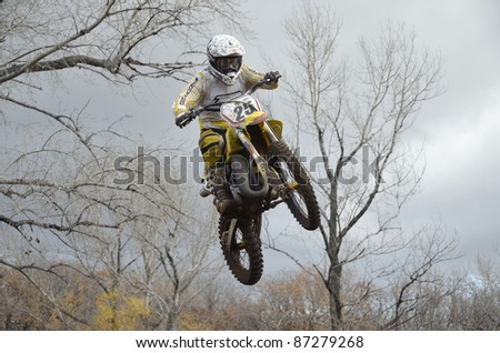 """RUSSIA, SAMARA, CHAPAYEVSK - OCTOBER 17: A jump rider unknown on the background an autumn forest the Open Cup """"Volga"""" motocross on October 17, 2011 in Chapayevsk, Samara, Russia - stock photo"""