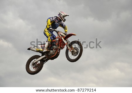 """RUSSIA, SAMARA, CHAPAYEVSK - OCTOBER 17: The spectacular jump motocross racer D. Vintaev on the background a stormy sky the Open Cup """"Volga"""" motocross on October 17, 2011 in Chapayevsk, Samara, Russia - stock photo"""
