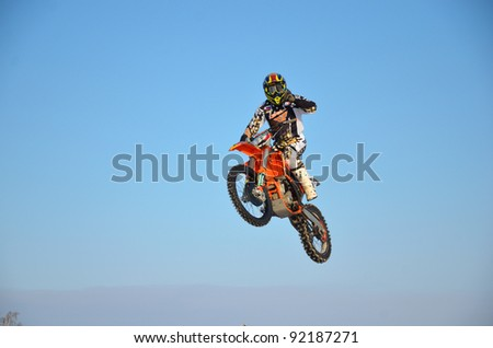 RUSSIA, SAMARA - JANUARY 3: Motorcyclist D. Vintaev performs a jump and waves to an audience (not pictured) during a motocross practice session on January 3, 2012 in Samara, Russia. - stock photo