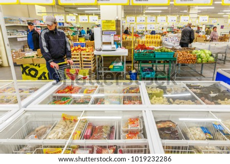 Russia, Samara, May 13, 2016: a young man with a stroller chooses frozen meat semi-finished products in a large supermarket. Text in Russian: instructions for using weights, product names.