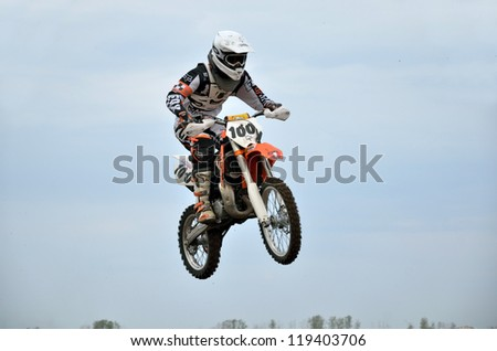 RUSSIA, SAMARA - MAY 6: MX  young participant E. Pershin on a motorcycle in the air, on the background of the cloudy sky  the 85 sm3 class the Regional Motocross on May 6, 2012 in Samara, Russia - stock photo