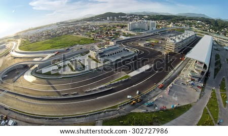 RUSSIA, SOCHI -?? JUL 28, 2014: Building site of stadium for racing near town and mountains at summer sunny day. Aerial view. (Photo with noise from action camera) - stock photo