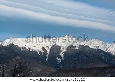 "Russia, Sochi, resort  ""Krasnaya Polyana"" (Red Meadow). View from the Olympic Stadium on ridge Achishkho and the Greater Caucasus Range. - stock photo"