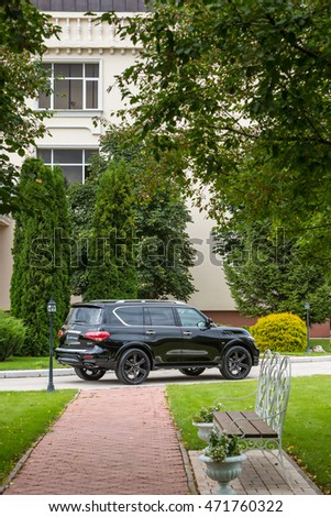 Russia, Togliatti - August 19, 2015: City test drive of Infiniti QX80 with tuning kit Missuro of LARTE Design Tuning Company. Beautiful house and summer garden on the background.