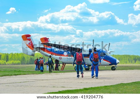 RUSSIA, TVERSKAYA OBLAST, BORKI AIRFIELD, May 8, 2016: Group of parachutists going to small aircraft AN-28 on a runway in a sunny and cloudy day. - stock photo