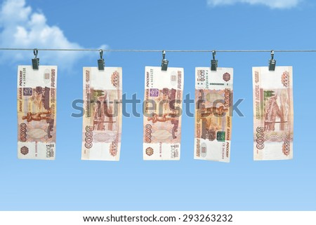 Russian banknotes, roubles hanging on the rope - stock photo