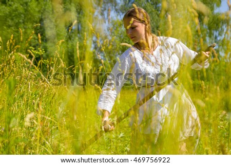 Russian beautiful folk girl in a white dress with a long scythe in a field in the village mows. Work in field