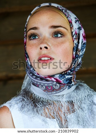 Russian beauty woman in the national patterned scarf - stock photo