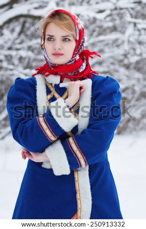 Russian beauty woman in traditional clothes against winter landscape