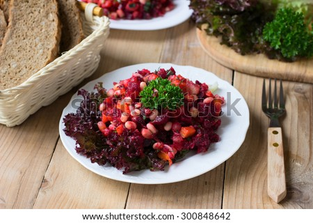 Russian beetroot salad Vinegret with white beans on wooden rustic table - stock photo
