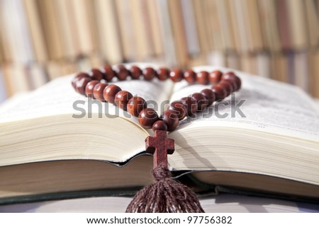 Russian bible and wooden rosary on the background of the library bookshelves - stock photo