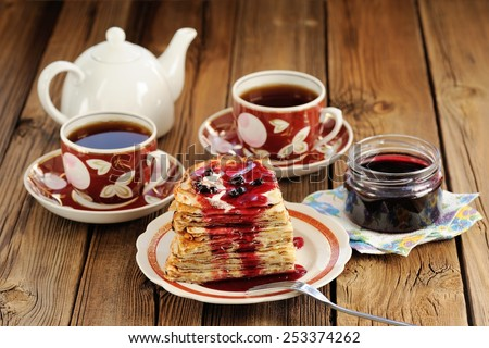 Russian bliny with currant jam, tea cups, pot on wooden background - stock photo
