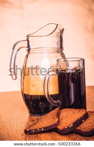 Russian brew in mug jug  and loaf of rye flour on wooden background