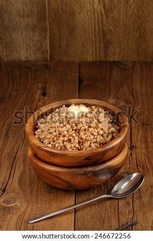 Russian buckwheat kasha in wooden bowl with bit of butter and old wood space background - stock photo