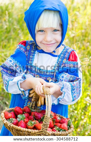 Russian children in traditional Russian costumes playing in the forest. - stock photo