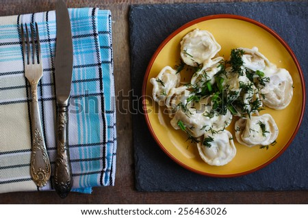 Russian dumplings with green onion on the wooden background - stock photo