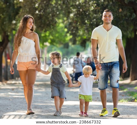 Russian family with children holding vacation day and smiling in park - stock photo