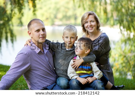 Russian family, young parents and two sons in autumn park - stock photo