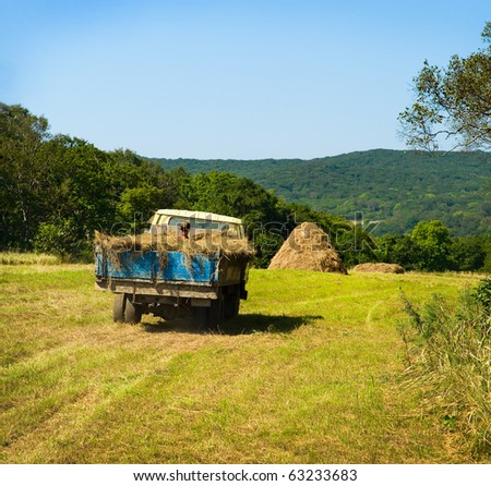 russian farmer riding old truck fully covered by hay - stock photo