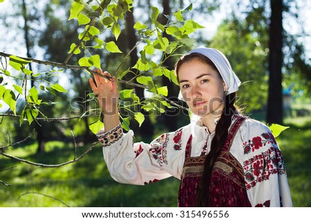 Russian girl in ethnic costume in village wood - stock photo