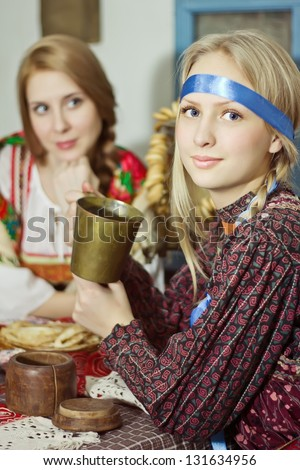 Russian girl in national costume with cup of tea and pancakes - stock photo