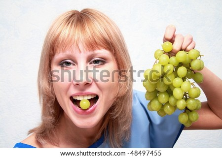 Russian girl smiling and eating grape. - stock photo