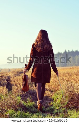 Russian girl with violin in nature - stock photo
